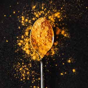 A spoon holding turmeric powder